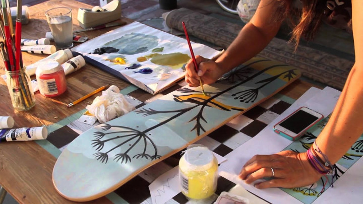 Person drawing a tree design on the bottom of a skateboard