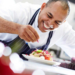 Chef sprinking the finishing garnish onto a plate of food