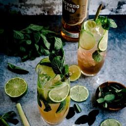 Two cocktails alongside a bottle of Havana Club