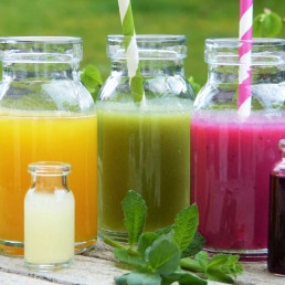 Yellow green and pink smoothies in glasses with straws